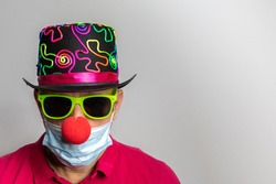 male person with surgery mask , clown nose and yellow sunglasses at carnival in covid19 and corona times. Horizontal