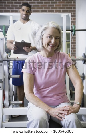 Male personal trainer with female client at gym