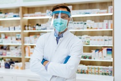 Male pharmacist with protective mask on his face, working at pharmacy. Medical healthcare concept.
