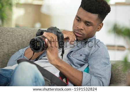 male photographer checking a dslr camera