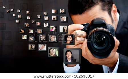 Male photographer holding the camera with pictures flying around
