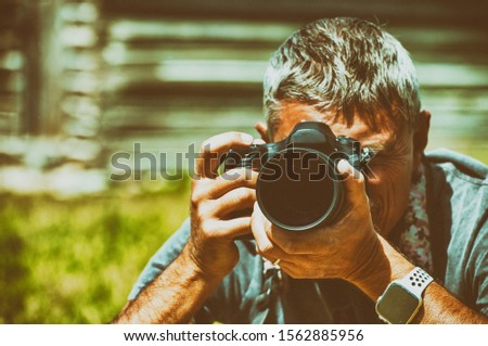 Male photographer observing natural landscape before making pictures.