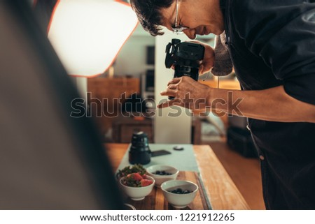 Male photographer shooting food on table. Professional food photographer making shot of food for advert. Male photographer taking pictures of food