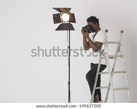 Male photographer taking photos with camera in studio #149637200