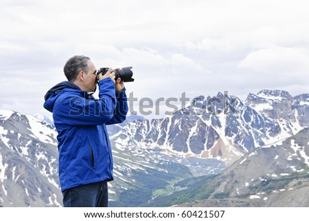 Male photographer taking pictures in Canadian Rocky Mountains in Jasper National Park