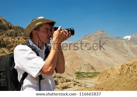 Male photographer tourist with camera in mountains
