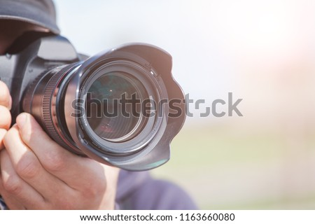 male photographer with a large professional camera looks into the viewfinder and takes pictures, toned #1163660080