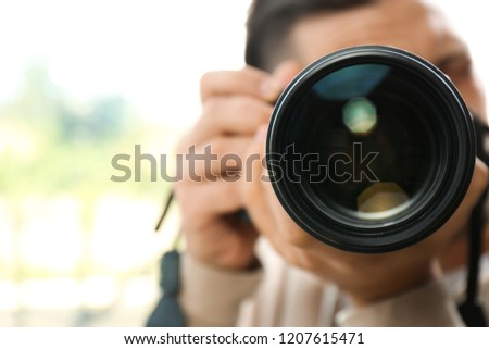 Male photographer with professional camera on blurred background. Space for text #1207615471