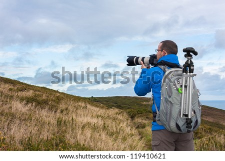 Male photographer with professional equipment is getting ready to take the photo
