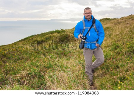 Male photographer with professional equipment is hiking  on a cliff