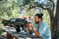 Male photographer working on a laptop outdoors in a camping. Freelancer, travel blogger working online at a laptop computer while hiking in the mountains outdoors. Work from anywhere in the world.