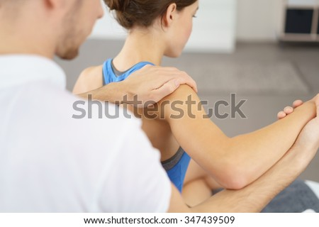 Male Physical Therapist Massaging the Injured Arm and Shoulder of a Young Woman Slowly. #347439509