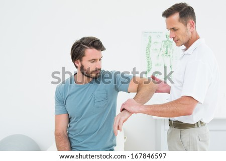 Male physiotherapist examining a young man\'s arm in the medical office