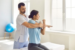 Male physiotherapist or chiropractor examining female patient's injured arm, stretching her muscles, helping her with medical exercise. Woman patient getting rehabilitation therapy in modern clinic