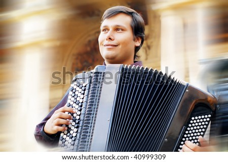 Male playing on the accordion against a grunge background - stock photo