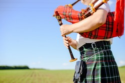 Male playing Scottish traditional pipes on green summer outdoors background, closeup image