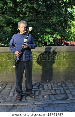 Male playing the flute on the street