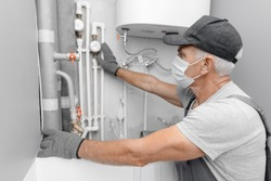 Male plumber in medical mask checks pipes for central hot and cold water supply of apartment.