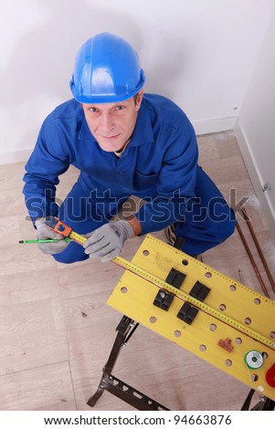 Male plumber using tape measure