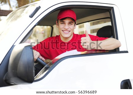 male postal delivery courier in a van showing thumb up hand sign - stock photo