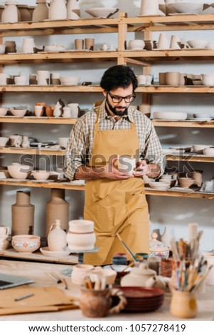 male potter with ceramic dishware in workshop #1057278419