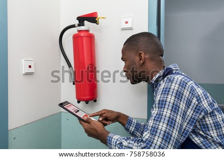 Male Professional Checking A Fire Extinguisher