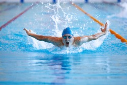 male professional competitive swimmer in swimming pool