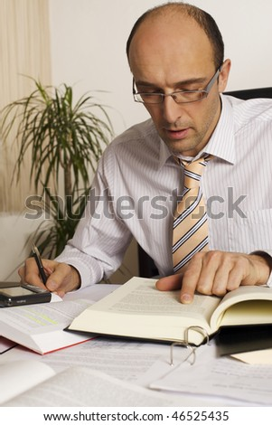 Male professional sitting at desk in office being busy studying books and papers.