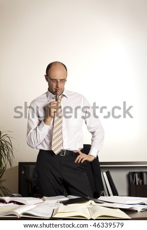 Male professional standing at office desk pondering over new business concepts.
