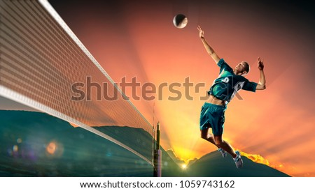 Male professional volleyball player in action at the sunset