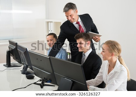 Male Professor Showing To Businesspeople On Computers At Desk