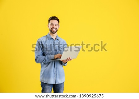 Male programmer with laptop on color background