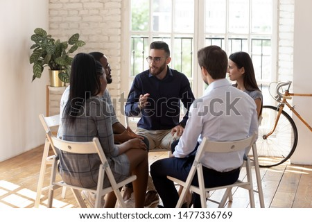 Male psychologist counselor therapist coach speak at group therapy session psychotherapy meeting supporting helping patients in substance addiction mental problem talk sit in circle in rehab concept