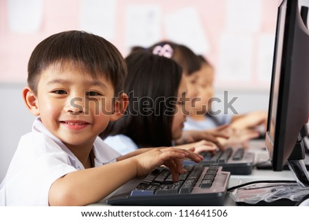 Male Pupil Using Keyboard During Computer Class In Chinese School Classroom - stock photo
