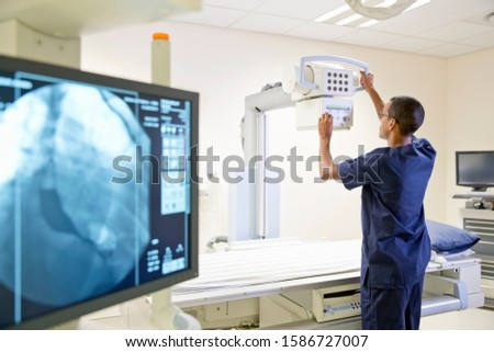 Male Radiographer Working In Hospital X Ray Department