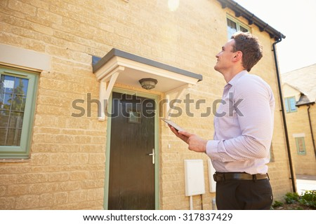 Male real estate agent looking up at a house exterior