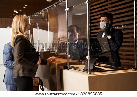 Male receptionist wearing a medical mask and rubber gloves while being at work and looking at the visitors with a phone in his hand Photo stock ©