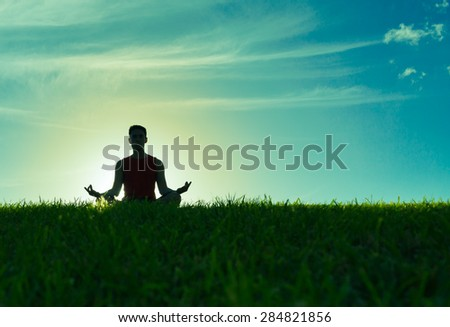 Male relaxing outdoors in the lotus position.