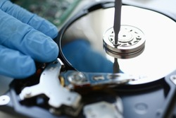 Male repairman wearing blue gloves dismantles specialized professional screwdriver hard drive. Performs fault diagnostics and performs urgent repairs recovery of lost data during deletion HDD closeup