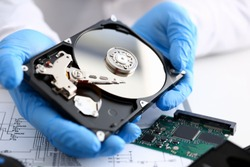 Male repairman wearing blue gloves holding hard drive from computer or laptop in hands. Performs fault diagnostics and performs urgent repairs recovery of lost data during deletion HDD closeup