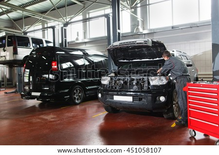 Male repairman working with motor in garage. Mechanic diagnosing problems under car hood. Fixing problems with car engine mechanic in garage.