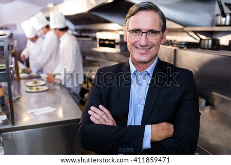 Male restaurant manager standing with arms crossed in commercial kitchen