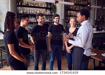 Male Restaurant Manager With Digital Tablet Giving Team Talk To Waiting Staff