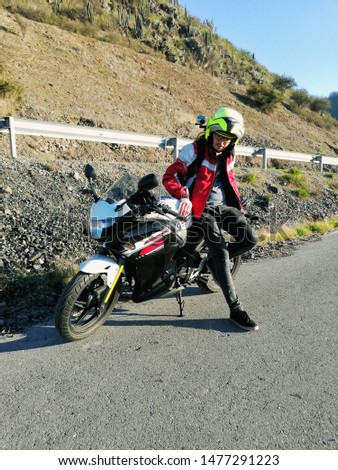 Male rider and his motorcyle in a rural road. Motorcycle safety equipment. Sport bike. Dry weather, sunny day.