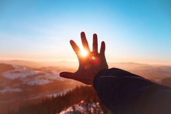 Male right hand covering the sun in Czechia mountines covered with snow at colorful sunset