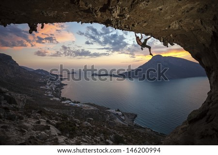 Male rock climber against picturesque view of Telendos Island at sunset. Kalymnos Island, Greece.
