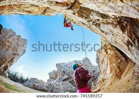 male rock climber climbs on a rocky wall at winter sunny day. Man climber in warm clothes on yellow cliff. #745589257