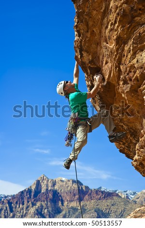 Male rock climber  clings to an overhang in Red Rock Canyon on a sunny day.