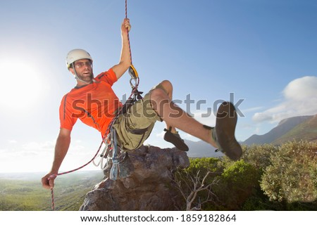Male rock climber in a helmet holding on to a rope while rappelling down a rock face. Photo stock ©