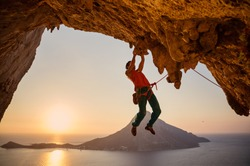 Male rock climber on challenging route on cliff at sunset
